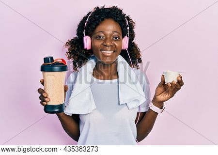 Young african american woman wearing sport clothes drinking a protein shake winking looking at the camera with sexy expression, cheerful and happy face.