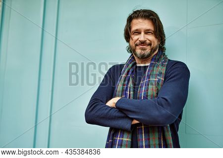 Middle age handsome man smiling with crossed arms leaning on the wall