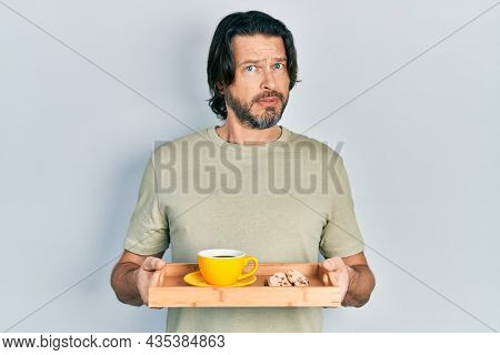 Middle age caucasian man holding breakfast tray with cookies and coffee in shock face, looking skeptical and sarcastic, surprised with open mouth