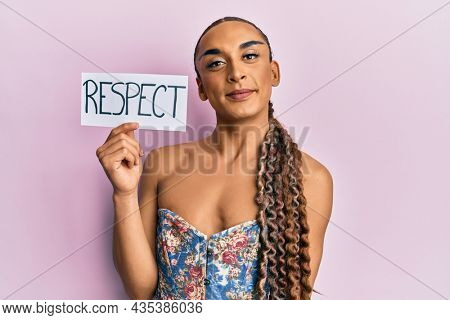 Hispanic transgender man wearing make up and long hair holding respect message looking positive and happy standing and smiling with a confident smile showing teeth