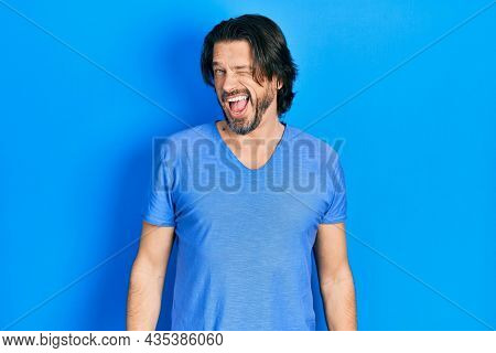 Middle age caucasian man wearing casual clothes winking looking at the camera with sexy expression, cheerful and happy face.