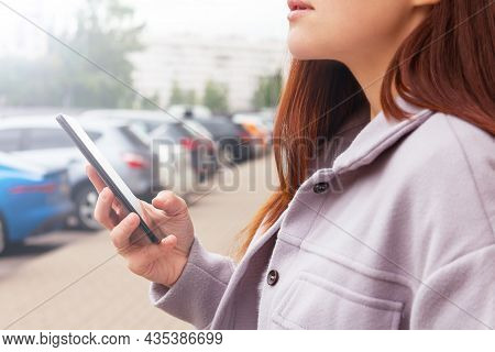Unrecognizable Caucasian Woman Holding Mobile Phone In Hand Standing Near Cars Parking Lot. Searchin