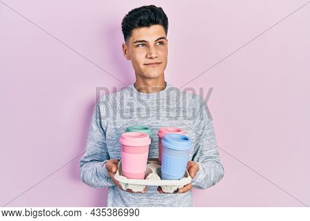 Young hispanic man holding tray with take away coffee smiling looking to the side and staring away thinking.