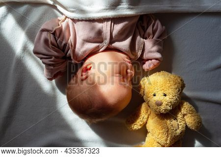 Adorable Caucasian Newborn Baby Girn In Pink Suit Sleeping In Her Bed On White Blanket With First To