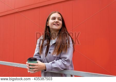 Beautiful Young Caucasian Woman Holding In Hands Glass Of Coffee Against Red Wall. Drinking Coffee C