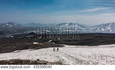 There Is Melted Snow On The Mountain Slope. Two People With Trekking Poles Rest While Climbing To Th