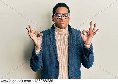 Young handsome hispanic man wearing elegant clothes and glasses relax and smiling with eyes closed doing meditation gesture with fingers. yoga concept.