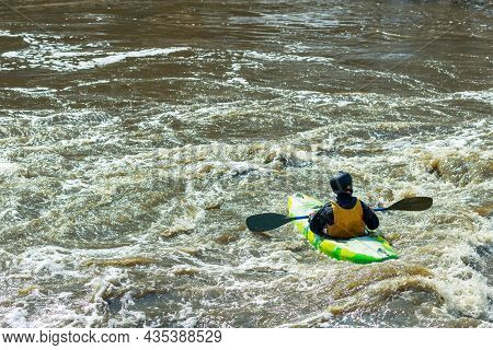 A Man Floating On The River On A Kayak. Stormy Water Is Dirty Around The Boat. Active Recreation On