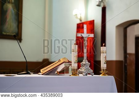 The Altar Of A Catholic Priest With A Bible On The Table.