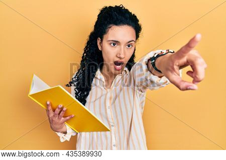 Young hispanic woman with curly hair holding book pointing with finger surprised ahead, open mouth amazed expression, something on the front
