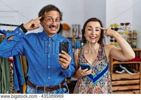 Middle age interracial couple at retail shop using smartphone smiling pointing to head with one finger, great idea or thought, good memory