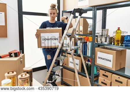 Young caucasian woman volunteer holding donations box pointing down looking sad and upset, indicating direction with fingers, unhappy and depressed.