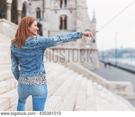 Young Redhead Hungarian Woman Pointing Into Distance At Parliament Building, Budapest, Hungary