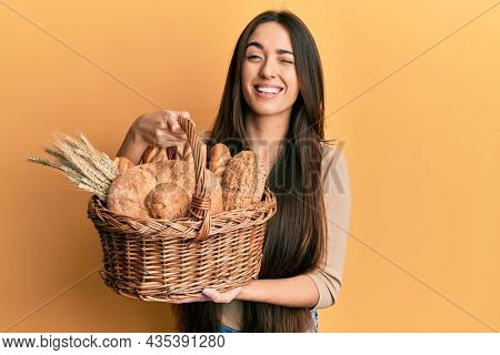 Young hispanic girl holding wicker basket with bread winking looking at the camera with sexy expression, cheerful and happy face.