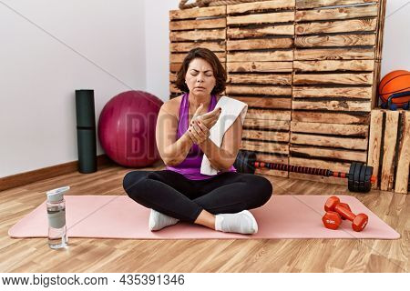 Middle age hispanic woman sitting on training mat at the gym suffering pain on hands and fingers, arthritis inflammation
