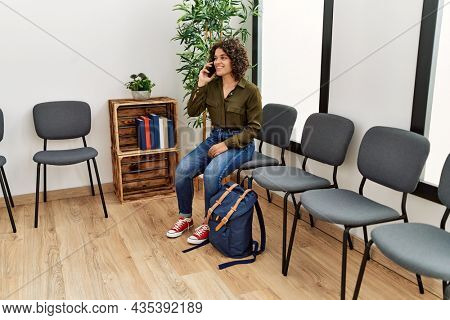 Young hispanic woman talking on the smartphone sitting on chair at waiting room