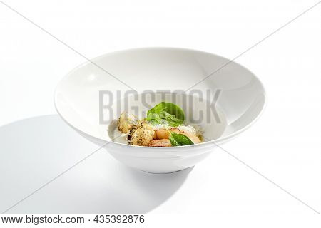 Gourmet dish - pan seared sea scallops with mashed potatoes, grilled cauliflowers on white plate. Scallops with vegetables and creamy espuma. Delicacy seafood in restaurant menu