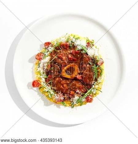 Traditional Italian dish - osso buco with risotto Milanese and cherry tomato and rucola. Ossobuco with saffron rice isolated on white background. Stewed meat on bone with yellow risotto