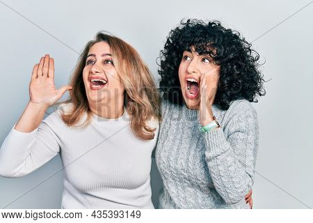 Middle east mother and daughter wearing casual clothes shouting and screaming loud to side with hand on mouth. communication concept.
