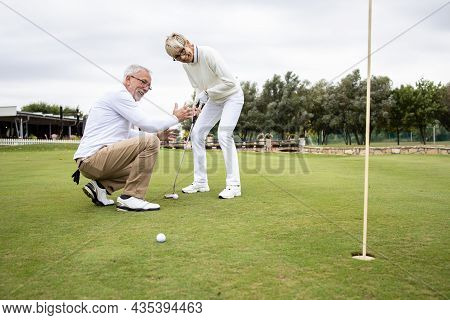 Senior Active People Having Fun At The Golf Course And Enjoying Free Time Outdoors.