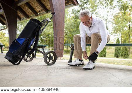 Senior Golfer Tying His Shoelace Before Golf Training.