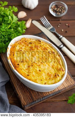 Homemade Shepherd's Pie In The Casserole Dish On A Dark Wooden Background. Traditional British Dish