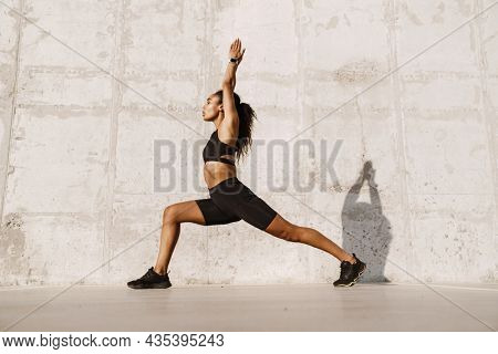 Black sportswoman doing exercise while working out at parking outdoors