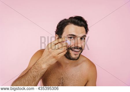 White shirtless man smiling while applying concealer with sponge isolated over pink background