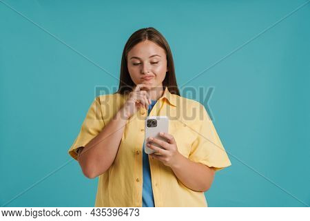 Young white woman wearing shirt grimacing and using cellphone isolated over blue background