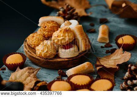 some different confections typicaly eaten in Spain on All Saints Day, such as Panellets, Huesos de Santo or Yemas de Santa Teresa, on a gray rustic table