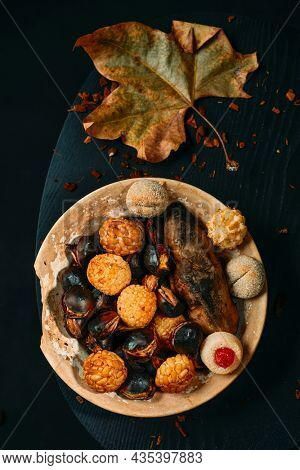 high angle view of a plate with food eaten in All Saints Day in Catalonia, Spain, in a party called Castanada, such as roasted chestnuts, sweet potato and panellets, a confection made with marzipan