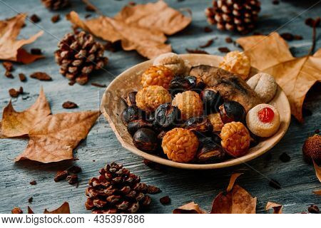 a plate with a roasted sweet potato, some roasted chestnuts and some panellets, typical confection of Catalonia, Spain, eaten traditionally in All Saints Day, in a party called Castanada, on a table