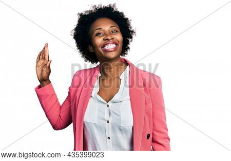 African american woman with afro hair wearing business jacket waiving saying hello happy and smiling, friendly welcome gesture