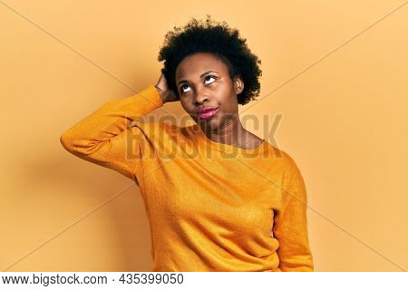 Young african american woman wearing casual clothes confuse and wondering about question. uncertain with doubt, thinking with hand on head. pensive concept.