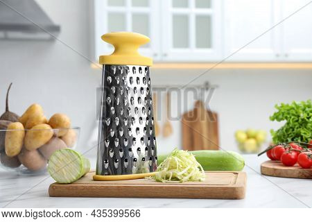 Grater And Fresh Zucchinis On White Table In Kitchen. Space For Text