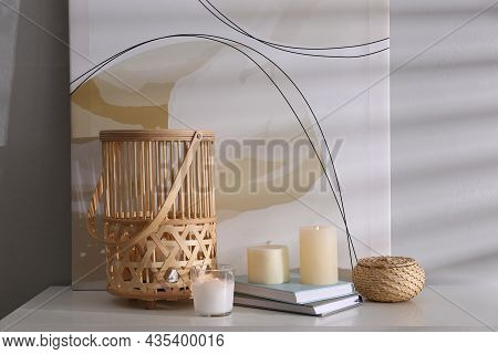 Burning Scented Candles And Books On White Table Near Light Wall