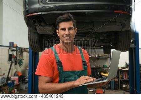 Mechanic With Laptop For Car Diagnostic At Automobile Repair Shop