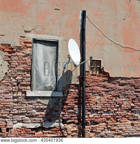 Satellite Dish For Receiving Tv Satellite Channels In A Decrepit House With A Cracked Wall