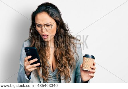 Young hispanic girl using smartphone and drinking a cup of coffee in shock face, looking skeptical and sarcastic, surprised with open mouth