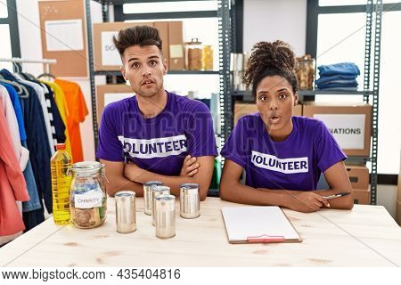 Young interracial people wearing volunteer t shirt at donations stand afraid and shocked with surprise expression, fear and excited face.