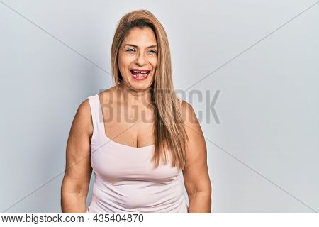 Middle age hispanic woman wearing casual style with sleeveless shirt winking looking at the camera with sexy expression, cheerful and happy face.