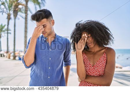 Young interracial couple outdoors on a sunny day tired rubbing nose and eyes feeling fatigue and headache. stress and frustration concept.