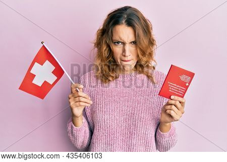 Young caucasian woman holding swiss flag and passport skeptic and nervous, frowning upset because of problem. negative person.