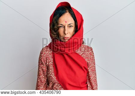 Middle age hispanic woman wearing tradition sherwani saree clothes skeptic and nervous, frowning upset because of problem. negative person.