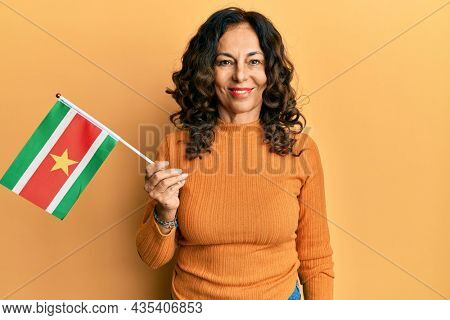 Middle age hispanic woman holding suriname flag looking positive and happy standing and smiling with a confident smile showing teeth