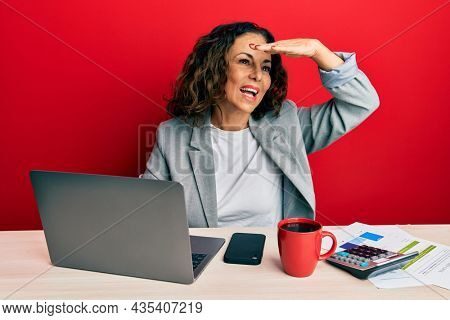 Beautiful middle age woman working at the office drinking a cup of coffee very happy and smiling looking far away with hand over head. searching concept.