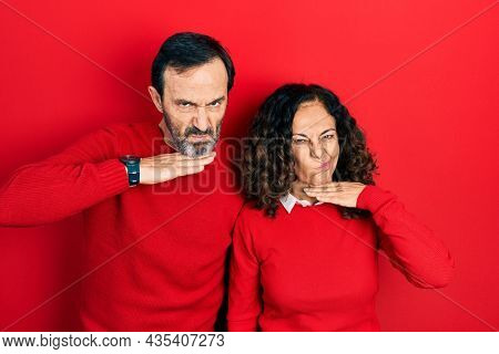 Middle age couple of hispanic woman and man hugging and standing together cutting throat with hand as knife, threaten aggression with furious violence