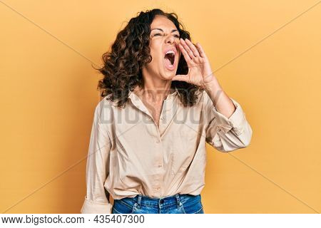 Middle age hispanic woman wearing casual clothes shouting and screaming loud to side with hand on mouth. communication concept.