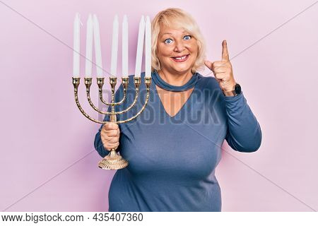 Middle age blonde woman holding menorah hanukkah jewish candle smiling with an idea or question pointing finger with happy face, number one