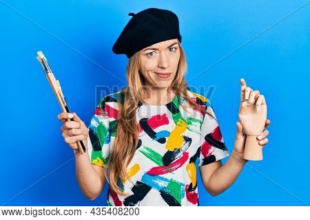 Young caucasian woman artist holding small wooden manikin and paintbrushes skeptic and nervous, frowning upset because of problem. negative person.